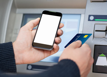 man holding mobile phone with isolated screen and a credit card at an ATM