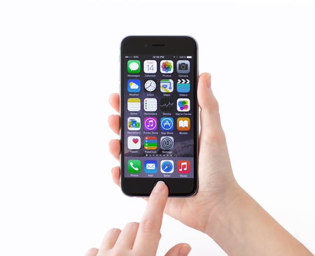 Alushta, Russia - November 14, 2014: Isolated new phone iPhone 6 Space Gray in a woman hand. iPhone 6 was created and developed by the Apple inc.