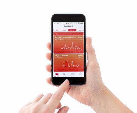 dedo: Alushta, Rusia - 14 de noviembre 2014: Nuevo iPhone 6 Gris Espacial con servicio de Apple de la Salud en la pantalla en una mano de mujer. iPhone 6 fue creado y desarrollado por Apple inc.