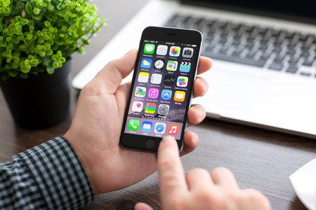 Alushta, Rusland - 20 november 2014: Man die nieuwe telefoon iPhone 6 Space Gray over de tafel met de Macbook. iPhone 6 werd gecreëerd en ontwikkeld door Apple inc.