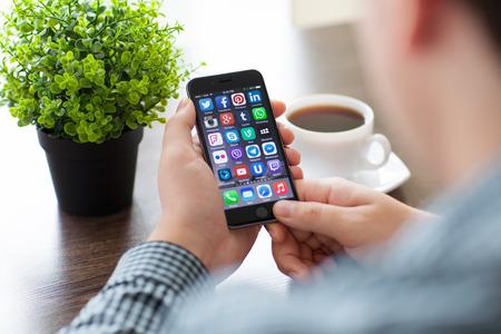 telegrama: Alushta, Rusia - 20 de noviembre 2014: Un conjunto de programas de marcas famosas de las redes sociales en el teléfono iPhone 6 en manos del hombre. iPhone 6 fue creado y desarrollado por Apple inc. Editorial