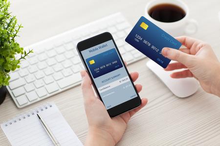 banco dinero: manos femeninas que sostienen el tel�fono con billetera m�vil para compras en l�nea sobre el escritorio Foto de archivo