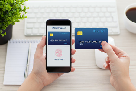 female hands holding phone with app mobile wallet and fingerprint for online shopping and credit card over the desk in the office