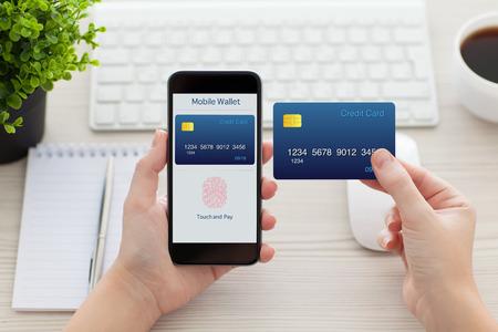 사무실에서 책상 위에 온라인 쇼핑과 신용 카드 응용 프로그램의 모바일 지갑과 지문 전화를 들고 여성의 손