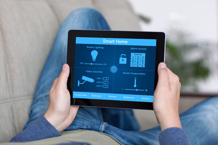 man lying on a sofa and holding a tablet with program smart home on the screen Foto de archivo