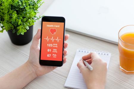 여성의 손을 건강 카드 모니터링을위한 응용 프로그램과 함께 전화를 들고와 노트북을 작성