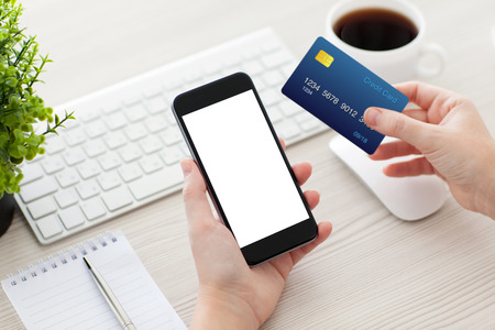 electronic card: female hands holding phone with isolated screen and a credit card over the desk in the office