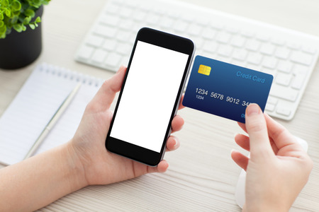 computer devices: female hands holding phone with isolated screen and a credit card over the desk in the office