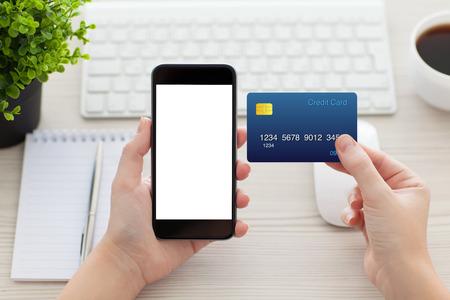 mains des femmes tenant un téléphone avec un écran isolé et une carte de crédit sur le bureau dans le bureau