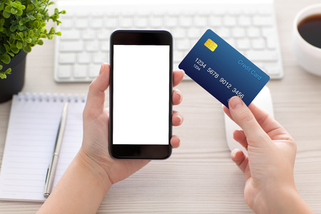 pay cuts: female hands holding phone with isolated screen and a credit card over the desk in the office