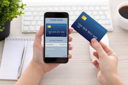 책상 위에 온라인 쇼핑 모바일 지갑으로 전화를 들고 여성의 손 스톡 콘텐츠