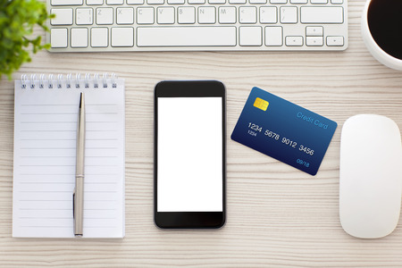 Telefoon met geïsoleerde scherm en een creditcard op de tafel in het kantoor Stockfoto - 38163335