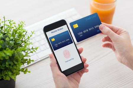 オフィスで机の上の女性両手携帯電話アプリおサイフケータイとオンライン ショッピングとクレジット カードの指紋