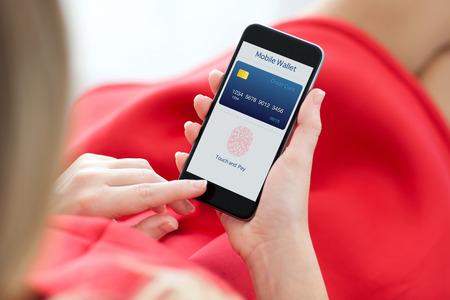 password: mujer de vestido rojo que sostiene un teléfono con billetera móvil app y huella digital para compras en línea