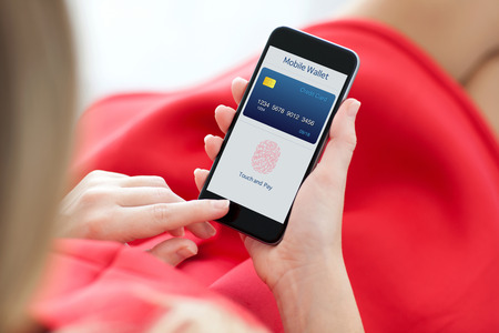 finance: woman in red dress holding a phone with app mobile wallet and fingerprint for online shopping