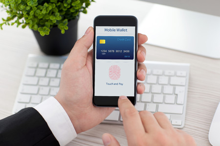 businessman sitting at the desk in office and holding phone with app mobile wallet and fingerprint for online shopping