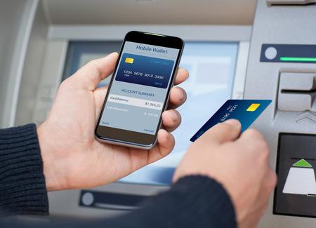 banco dinero: hombre que sostiene el tel�fono con billetera m�vil y tarjeta de cr�dito en la pantalla en el contexto de la ATM Foto de archivo