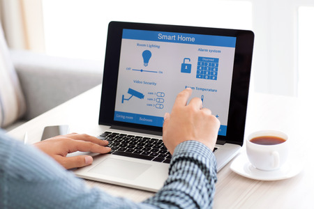 man sitting at a laptop with the program smart home on the screen
