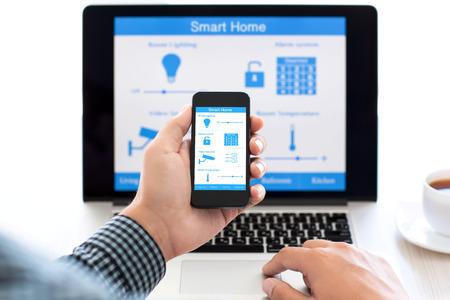 컴퓨터의 배경 화면에 프로그램 스마트 홈과 전화를 들고 남자