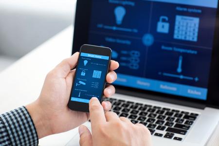 edificios: hombre que sostiene el tel�fono con el programa casa inteligente en la pantalla en el contexto de la computadora Foto de archivo
