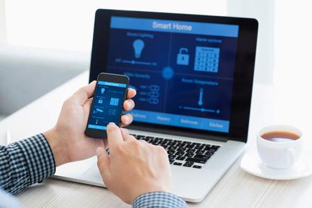 sistema: hombre que sostiene el tel�fono con el programa casa inteligente en la pantalla en el contexto de la computadora Foto de archivo