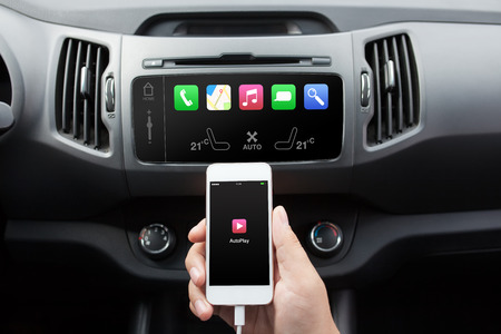 connect: man connecting phone with auto play to the car media system Stock Photo