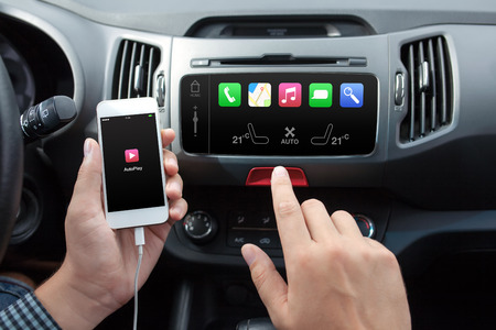 wireless connection: man connecting phone with auto play to the car media system Stock Photo
