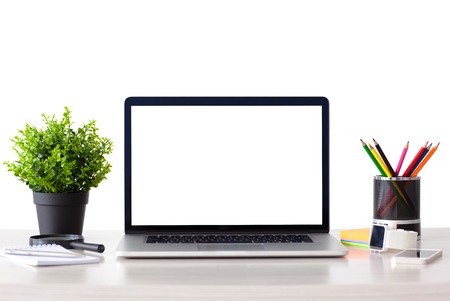 laptop computer with isolated screen stands on the table in the office with phone and watch