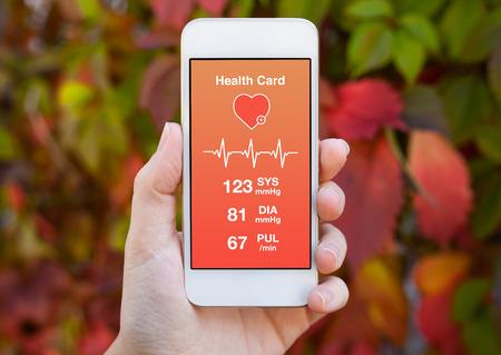 색깔 된 잎의 배경에 건강 카드와 함께 흰색 전화를 들고 여성 손