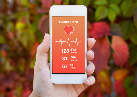 health information: female hand holding a white phone with health card on a background of colored leaves