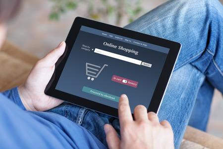 男はソファーに座っているとタブレットのオンライン shoppind を作る