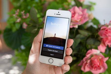 아루샤 러시아 2014년 9월 30일 : 여자가 화면에 소셜 네트워킹 서비스 인스 타 그램에 아이폰 5 S를 들고. 아이폰은 생성과 애플 INC에 의해 개발되었다.