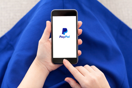 paypal: Alushta Russia December March 2014: Woman holding a iPhone 6 Space Gray with service PayPal on the screen. iPhone 6 was created and developed by the Apple inc.