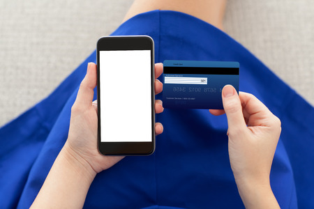 pay cuts: woman in a blue dress holding a phone with isolated screen and credit card