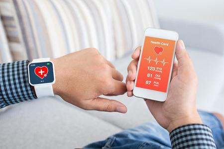 携帯アプリ健康センサー タッチ携帯電話およびスマートな時計を保持している男性の手