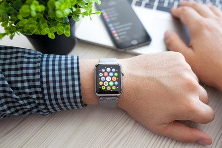 manzanas: Alushta, Rusia - 14 de agosto de 2015: La mano del hombre con Apple Watch y aplicaci�n del icono en la pantalla. Apple Seguir fue creado y desarrollado por Apple inc. Editorial