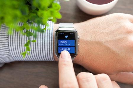 manzana: Alushta, Rusia - 1 de septiembre de 2015: La mano del hombre con Apple Watch y servicio de redes sociales aplicación de Twitter en la pantalla. Apple Seguir fue creado y desarrollado por Apple inc. Editorial