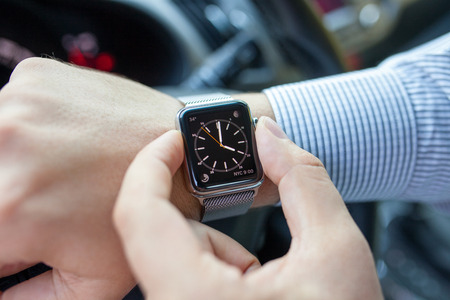 Alushta, Russia - September 3, 2015: Man hand in the car with Apple Watch and Clock on the screen. Apple Watch was created and developed by the Apple inc.
