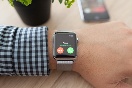 manzana: Alushta, Rusia - 11 de agosto 2015: La mano del hombre con Apple Watch y llamada de tel�fono en la pantalla. Apple Seguir fue creado y desarrollado por Apple inc.
