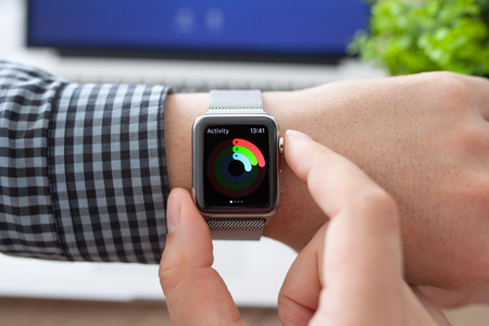 Alushta, Russia - August 11, 2015: Man hand in Apple Watch with app Activity on the screen and Macbook. Apple Watch was created and developed by the Apple inc.