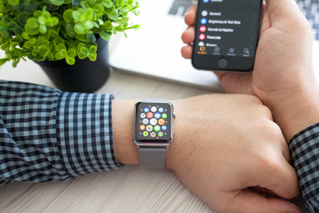 media gadget: Alushta, Russia - August 14, 2015: Man hand with Apple Watch and app Icon on the screen. Apple Watch was created and developed by the Apple inc.