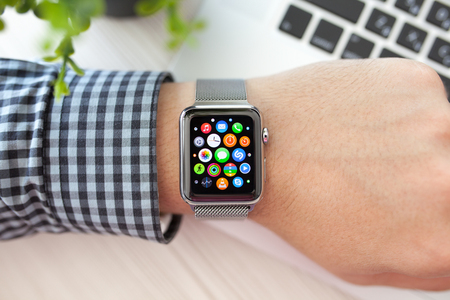 apple computers: Alushta, Russia - August 29, 2015: Man hand with Apple Watch and app Icon on the screen. Apple Watch was created and developed by the Apple inc.