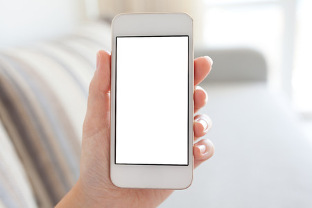 media room: female hand holding white phone with isolated screen on the background of the room Stock Photo