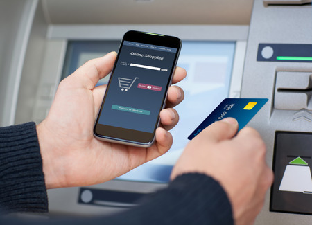 man holding phone with app online shopping on the screen and a credit card at an ATM