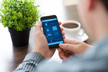 sistema: hombre que sostiene el tel�fono con el programa de casa inteligente en la pantalla en la oficina