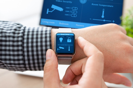 main de l'homme dans la montre avec le programme maison intelligente sur l'écran sur le fond de l'ordinateur