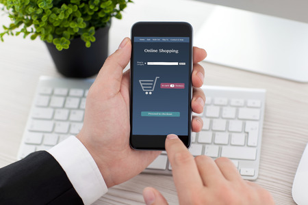 businessman sitting at the desk in office and holding phone with app online shopping on the screen Stockfoto
