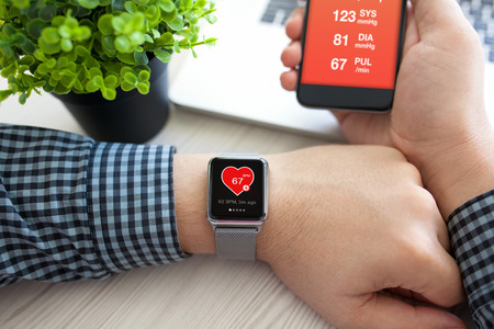 screen: Man hands with watch and phone with app health on the screen Stock Photo