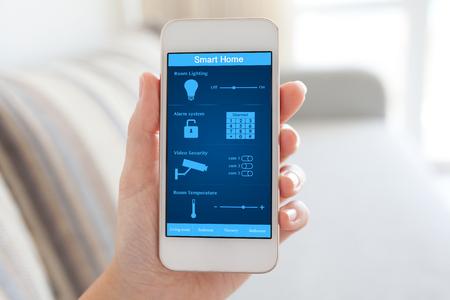 ルームでスマート ホーム画面上に白い携帯電話を保持している女性の手