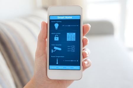 female hand holding white phone with smart home on the screen in the room Stockfoto